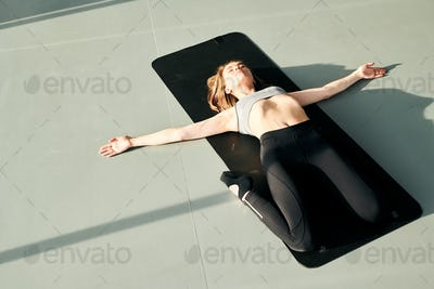 Pretty active girl in tracksuit lying on black mat with her arms outstretched