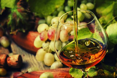 Cognac Pour In Glass, Grapes And Vine