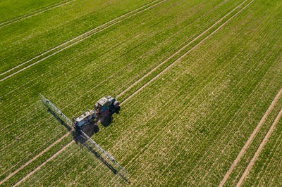 tractor spraying herbicides on field, Tractor Spraying Chemicals on Field - GMO Crops