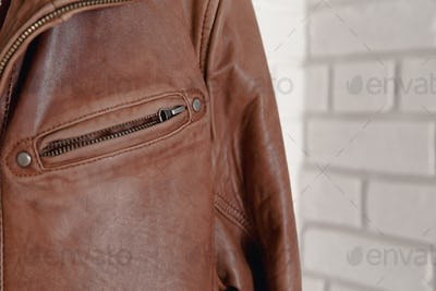 Brown leather jacket hanged on white wall hanger