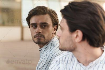 Photo of focused man wearing striped shirt looking at himself in mirror indoors