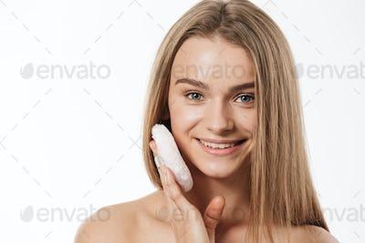 Beauty portrait of young half-naked woman applying makeup with sponge