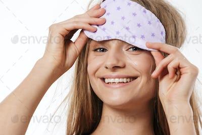 Beauty portrait of blonde half-naked woman wearing sleeping mask smiling
