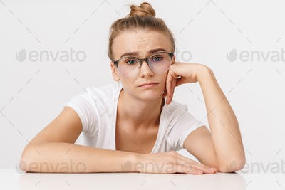 Photo of nice unhappy woman looking at camera while leaning on table