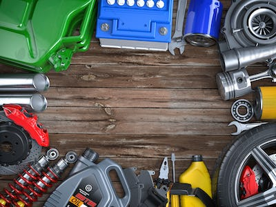 Car parts, spares and accesoires on wooden table. Auto service and car repair workshop concept.