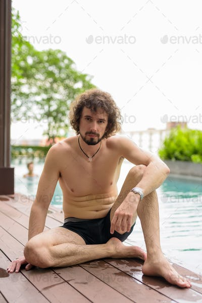 Handsome bearded man shirtless relaxing beside the swimming pool