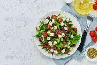 Greek Salad with feta and tomatoes, dieting food on white background copy space top view