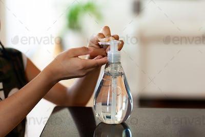 Black African American children hand using antibacterial antiseptic hand sanitizer gel
