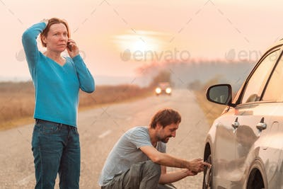 Couple repairing car flat tire on the road