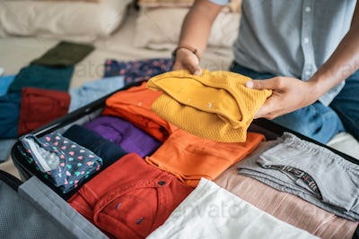 young man preparing her clothes put in the suitcase