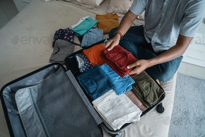 asian man putting her clothes in the suitcase