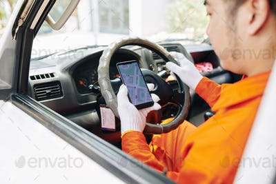 Delivery man checking map on smartphone