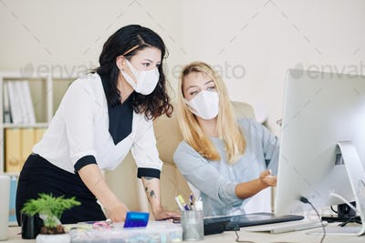 Female entrepreneurs in medical masks working in office