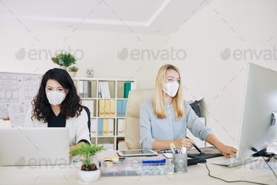 Graphic designers working in medical masks
