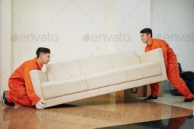 Workers carrying heavy couch