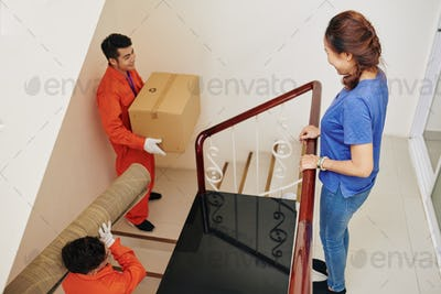Movers carrying stuff in new apartment