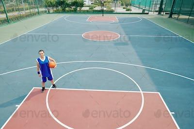 Woman playing basketball alone