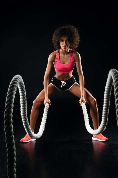 Image of african american sportswoman doing exercise with battle ropes