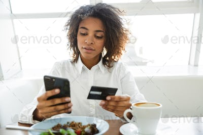 Portrait of young woman using cellphone and credit card in cafe