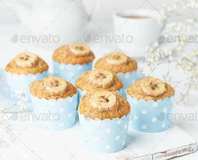 Banana muffin, cupcakes in blue cake cases paper, side view, close up, white concrete table