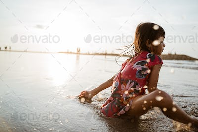 Asian little girl sitting on sand in the beach while playing water