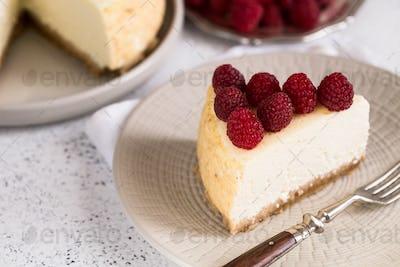 Slice Of Classical New York Cheesecake with raspberries
