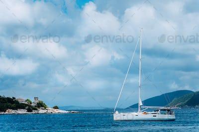 Summer scenery of port Fiskardo. White sail boat in beautiful tranquil bay opposite rocky seashore