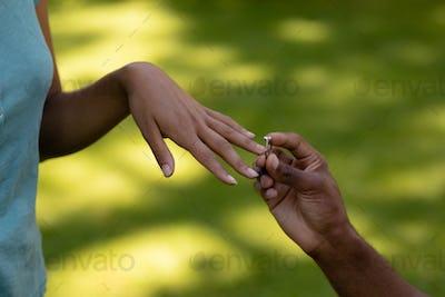 Young man putting wedding ring woman finger