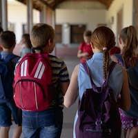 Group of schoolchildren walking in an outdoor corridor at elementary school