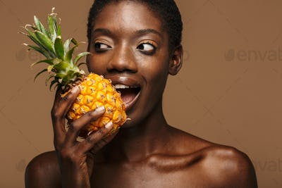 Beauty portrait of young half-naked african woman holding pineapple
