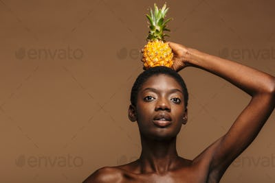 Beauty portrait of half-naked african woman holding pineapple on her head