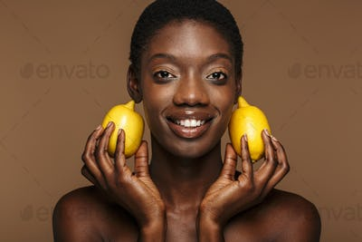 Beauty portrait of pretty young half-naked african woman holding lemons