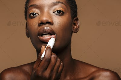 Beauty portrait of young half-naked african woman putting on lipbalm