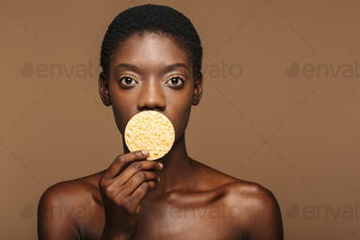 Beauty portrait of young half-naked african woman holding makeup sponge