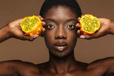 Beauty portrait of half-naked african woman holding kiwano horned melon