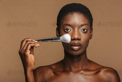 Beauty portrait of pretty half-naked african woman holding makeup brush