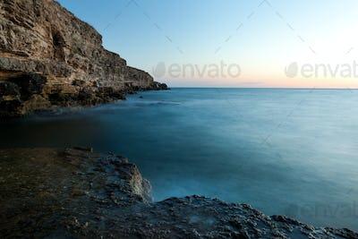 Beautiful sunset over wavy stormy Black sea rocky coastline in Crimea on summer day
