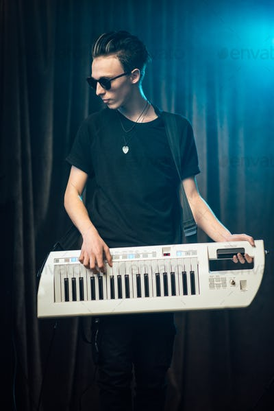 Trendy young man playing on an electronic keyboard
