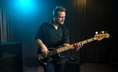 Male guitarist playing an electric bass guitar