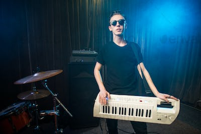 Man in sunglasses playing on electronic keyboard