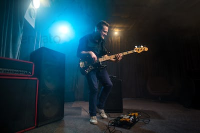 Musician playing an electric Bas-guitar on stage