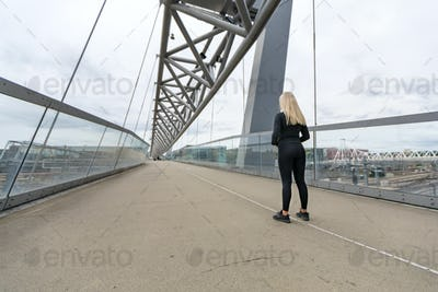 Fitness woman runner Standing On Bridge in Modern Looking City