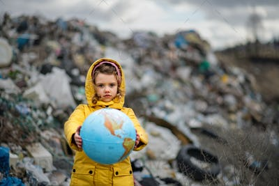 Small child holding globe on landfill, environmental pollution concept