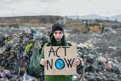 Woman activist with placard poster on landfill, environmental pollution concept