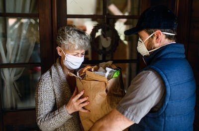 Courier delivering shopping to senior woman with face mask, corona virus and quarantine concept