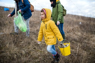 Group of activists picking up litter in nature, environmental pollution concept
