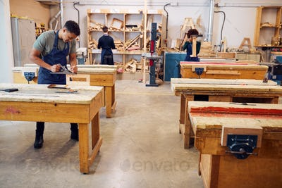 Wide Angle View Of Carpentry Workshop With Students Studying For Apprenticeship At College