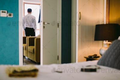 man getting dressed in hotel