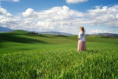 Woman among Tuscany rolling fields