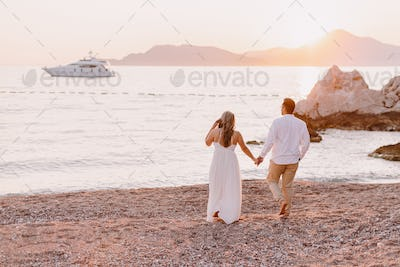 Couple relax on beach at sunset with yacht view